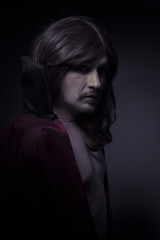 man with long hair and black coat