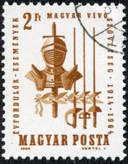 stamp printed by Hungary, shows Armor, saber, sword and foil