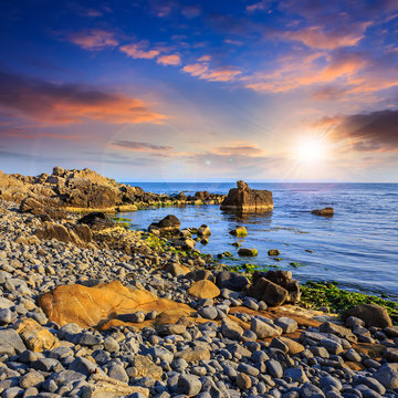 sea wave breaks about boulders at sunset