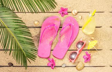 Beach, palm tree leaves, sand, sunglasses and flip flops