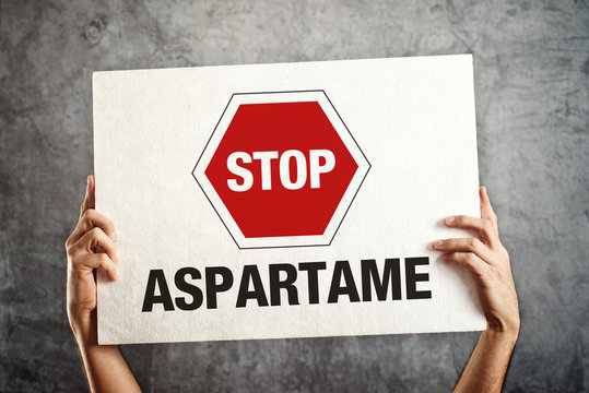 Hands holding banner with STOP ASPARTAME message