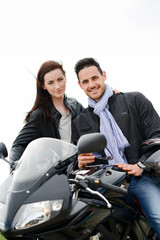 happy young lovers couple riding a motorbike on a vacation trip