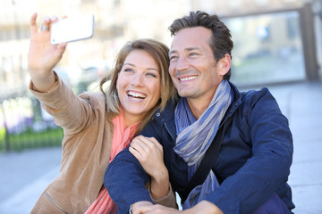 Mature couple taking picture with smartphone