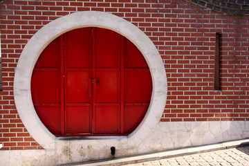red chinese circle door on brick wall