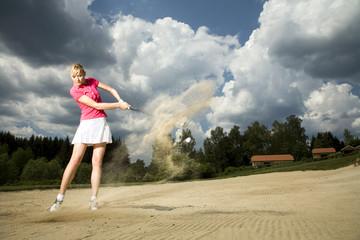 Junge Frau, die Golf spielen