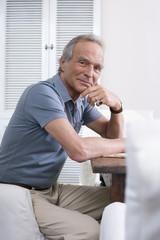 Senior Mann sitzt am Tisch,Hand am Kinn,Portrait