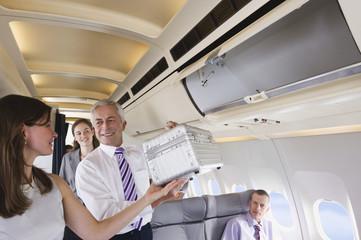 Deutschland,Bayern,München,Passagiere Entfernen Handgepäck vom Regal in der Business-Class- Flugzeug-Kabine