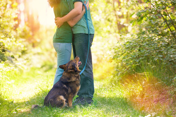 Young couple in love hugging in the forest. Dog sitting near