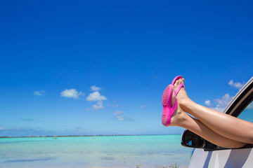 Close up pink flip flops from a car background of tropical beach