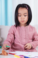 Sweet little asian girl with crayons