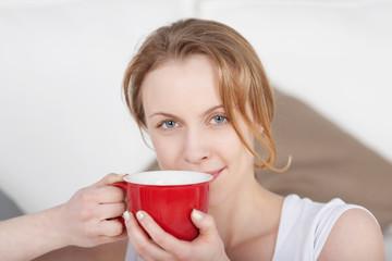 schöne blonde frau mit einer roten tasse kaffee