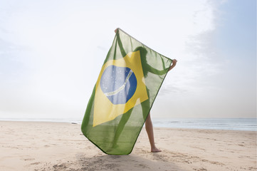 Young attractive girl on beach with Brazil flag