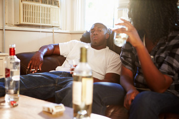 Couple Sitting On Sofa With Bottle Of Vodka And Cigarettes