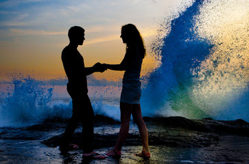 young couple standing and holding in hand on the shore
