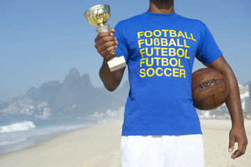 Champion Brazilian Soccer Player Holding Trophy and Soccer Ball