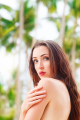 Beautiful young woman with long hair in black bikini relaxes und