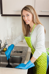 woman cleaning pipe with plunger