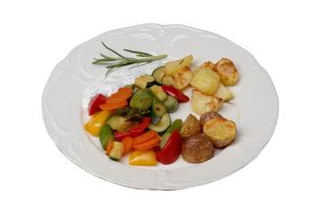 isolated plate with vegetables and oven potatoes