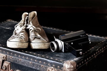 Sneakers and movie camera on suitcase