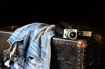 Pair of jeans and movie camera on old suitcase