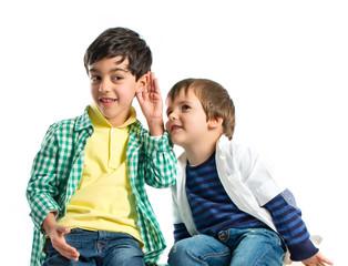 Kids whispering over white background