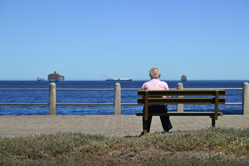 Old man sitting by the see and viewing ships