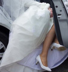 Bride getting out of car, view of her white shoes