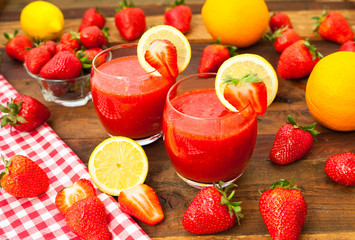 Strawberry smoothies with fresh fruits on wooden background