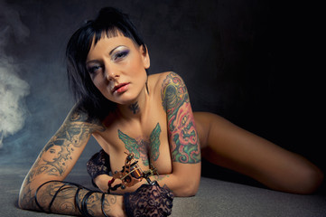 Beautiful woman with many tattoos indoors