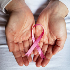 cancer concept, pink ribbon in the hands