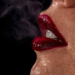 Macro photo of wet woman's lips with smoke on background