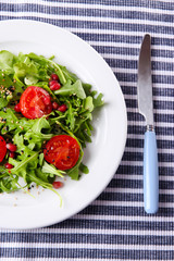 Green salad made with  arugula, tomatoes and sesame