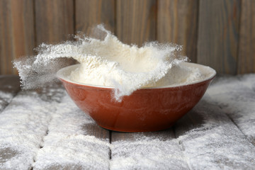 Flour in bowl on table on wooden background
