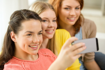 smiling teenage girls with smartphone at home