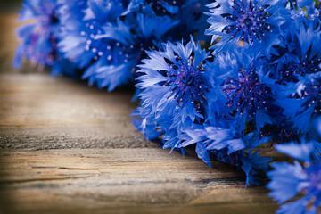 Fotoväggar - Cornflowers over wooden background. Wild blue flowers