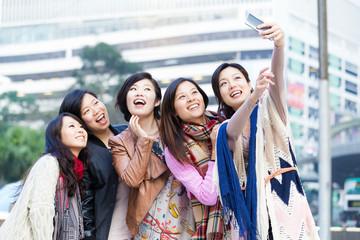 Young female friend taking selfie in Hong Kong