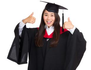 Smiling graduate girl thumb up