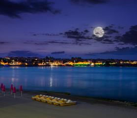 calm sea waves on city beach at night