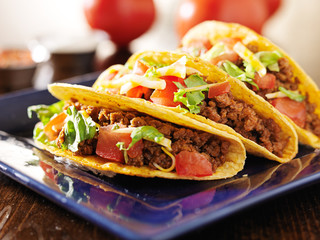 Wall Mural - three beef tacos with cheese, lettuce and tomatos