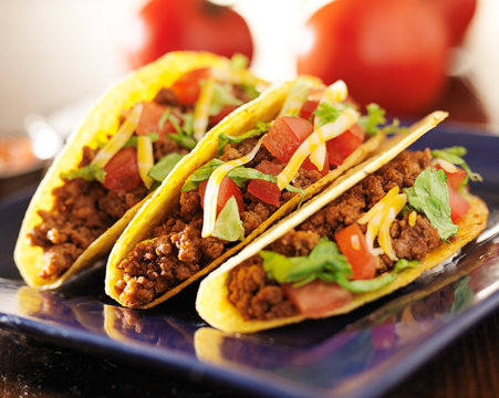 three beef tacos with cheese, lettuce and tomatos