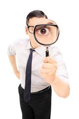 Obraz Man looking through a magnifying glass - fototapety do salonu