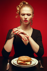 Unhappy luxurious red-haired model trying to eat burger