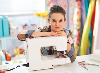 Portrait of happy seamstress with sewing machine