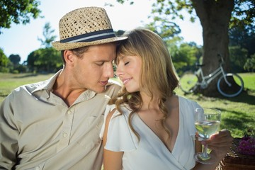 Cute couple drinking white wine on a picnic smiling at each othe