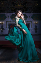 Beautiful woman in a green long dress