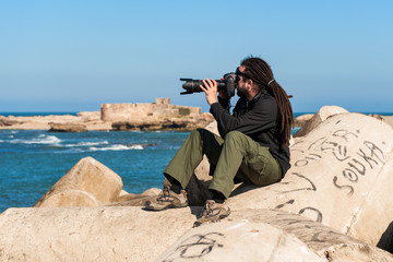 Man with dreadlocks taking a photograph at a seaside