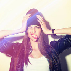 Hipster girl with beanie holding head making funny face