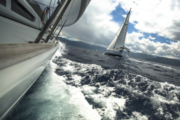 Sailing ship yachts in the sea at race in stormy weather.