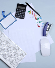 Office table with stationery accessories, keyboard and paper,