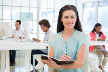 Attractive businesswoman writing in notebook and smiling to came